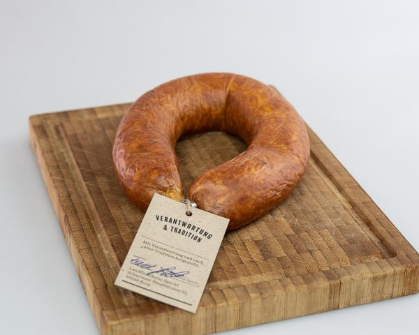 Mettwurst im Ring geräuchert auf einem rustikalen Holzbrett