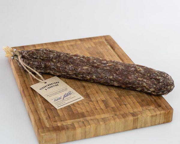 Luftgetrocknete Salami auf einem Holzbrett Landfleischerei