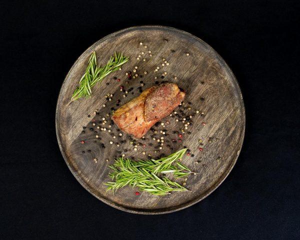 Pfefferfilet geräuchert mit Rosmarin Zweigen auf einem rustikalen Holzbrett