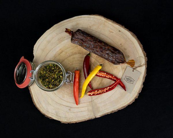 Chilli Salami geräuchert auf einem rustikalen Holzbrett mit Chilli Gewürzen
