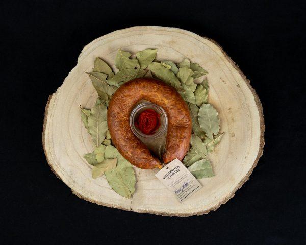 Mettwurst im Ring geräuchert auf einem rustikalen Holzbrett mit Gewürzen