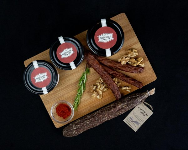 Kleines Wurstpaket dekorativ platziert; Salami luftgetrocknet, Whiskey Nussknacker